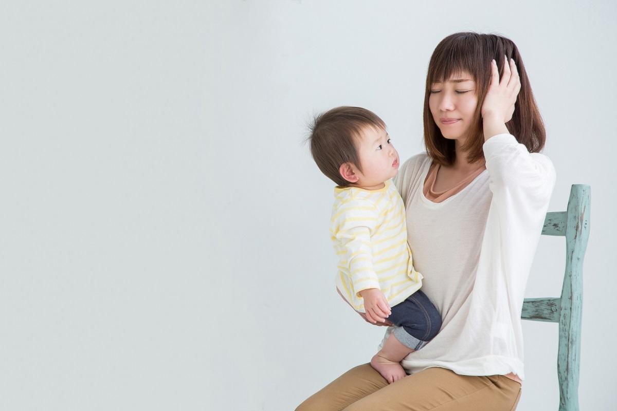 赤ちゃんを抱っこしながら頭を抱える女性