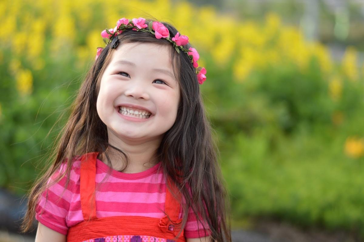 花かんむりをつけて路上で笑っている子供