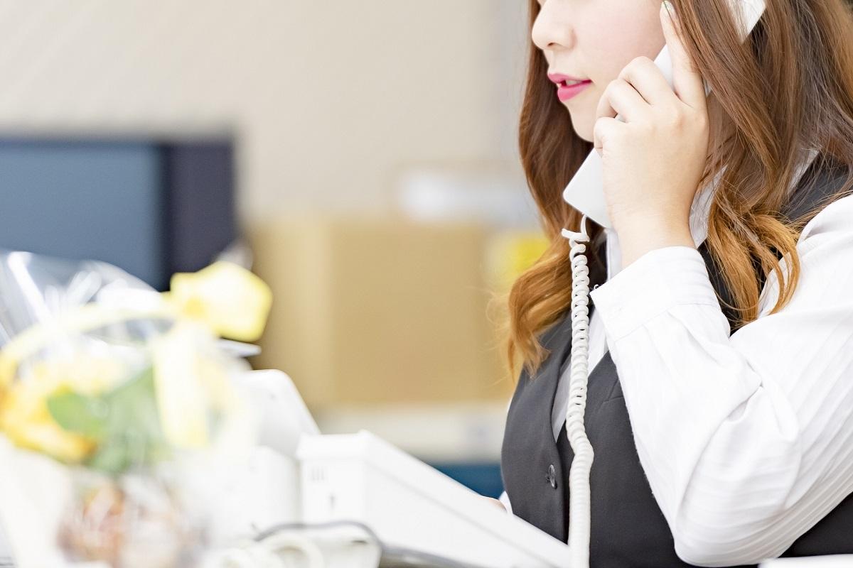 電話を掛ける事務風の女性